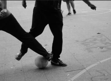 voetballer speelt bal door de benen